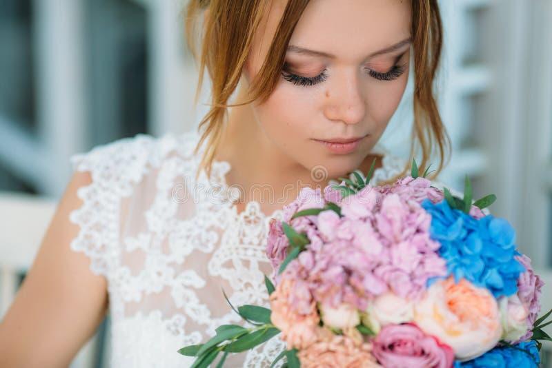 Un modelo con maquillaje en colores naturales y pestañas grandes mira un ramo de flores Una muchacha hermosa inhala fotografía de archivo