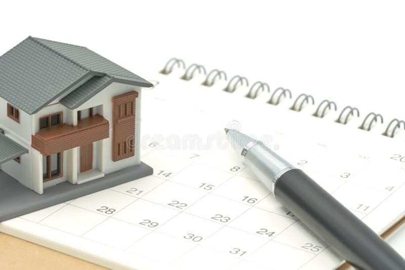 Un modelo modelo de la casa se pone en un calendario y una pluma como concepto de las propiedades inmobiliarias de la propiedad d fotografía de archivo