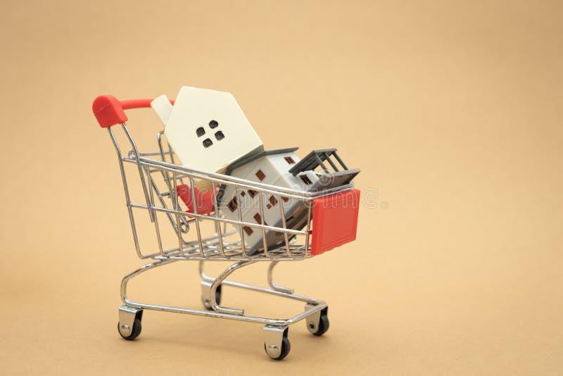 Un modelo modelo de la casa se pone en un carro de la compra en la alameda el usar como concepto del negocio del fondo y concepto imagen de archivo