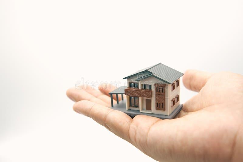 Un modelo modelo de la casa se pone en las manos de hombres de negocios asiáticos el usar como concepto del negocio del fondo y c fotos de archivo libres de regalías