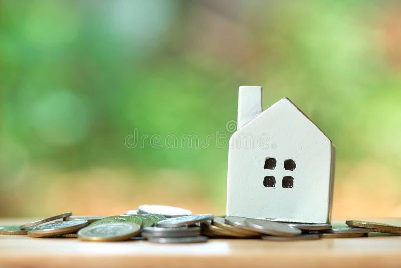Un modelo modelo de la casa se pone en una pila de monedas el usar como concepto del negocio del fondo y concepto de las propieda fotografía de archivo libre de regalías