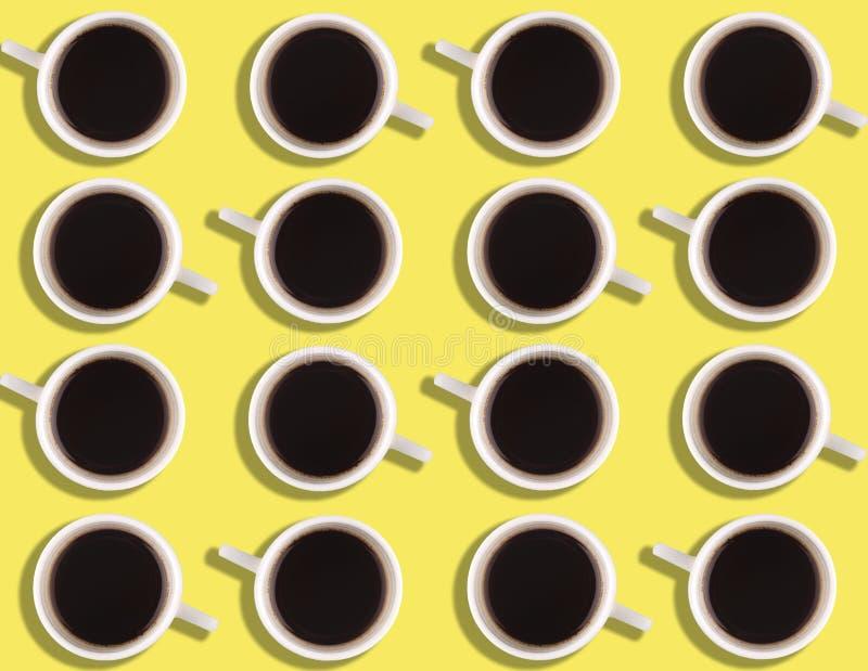 Un modelo de las pequeñas tazas de café en un fondo coloreado brillante fotografía de archivo libre de regalías