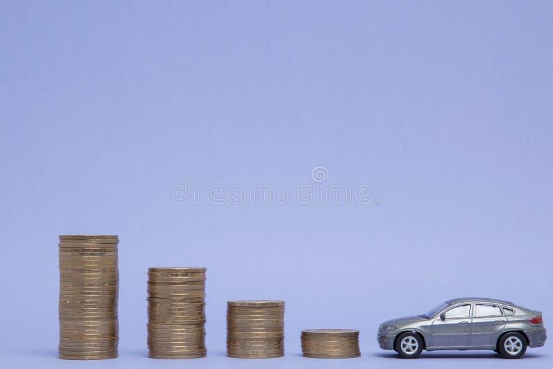 Un modelo gris de un coche con las monedas bajo la forma de histograma en un fondo p?rpura Concepto de pr?stamos, ahorros, seguro imagen de archivo libre de regalías