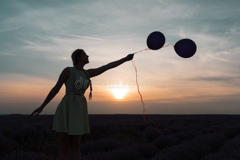 Un modelo hermoso con las trenzas largas se coloca en un campo de la lavanda Controles dos globos en sus manos Foto de la silueta fotografía de archivo