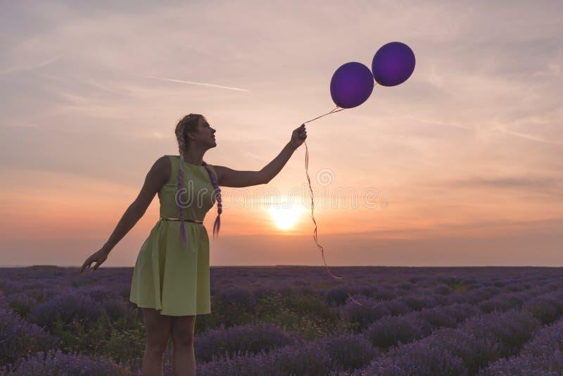 Un modelo hermoso con las trenzas largas se coloca en un campo de la lavanda Controles dos globos en sus manos Puesta del sol en  imágenes de archivo libres de regalías