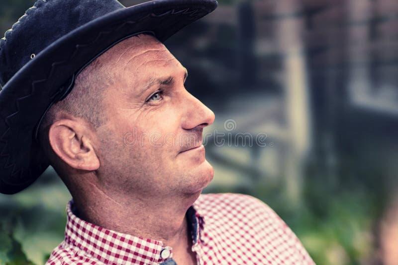 Un modelo masculino en una camisa de tela escocesa, sombrero fotografía de archivo libre de regalías