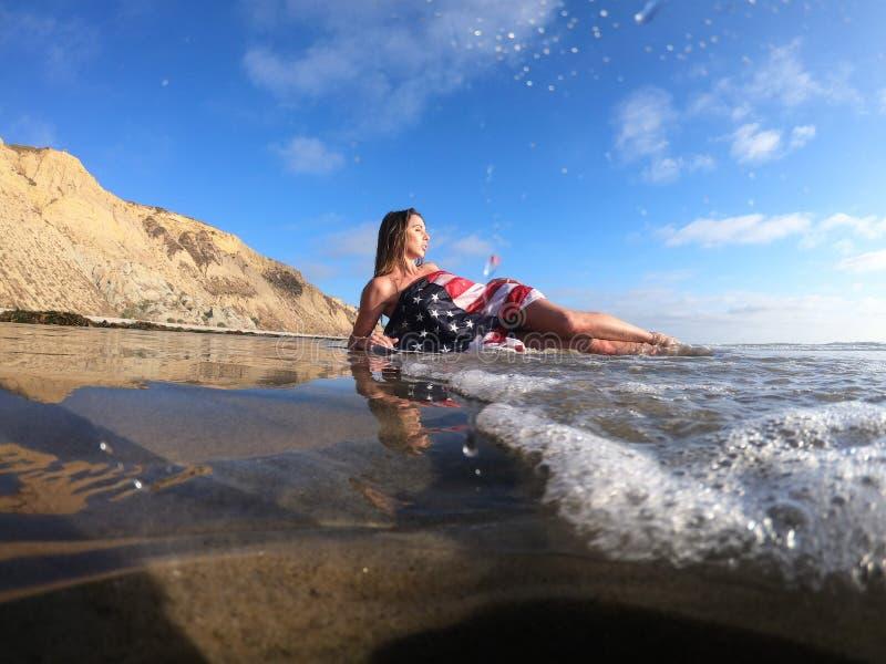 Un modelo moreno precioso Poses Nude At la costa con una bandera americana imágenes de archivo libres de regalías