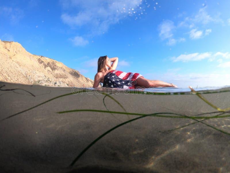 Un modelo moreno precioso Poses Nude At la costa con una bandera americana imagen de archivo