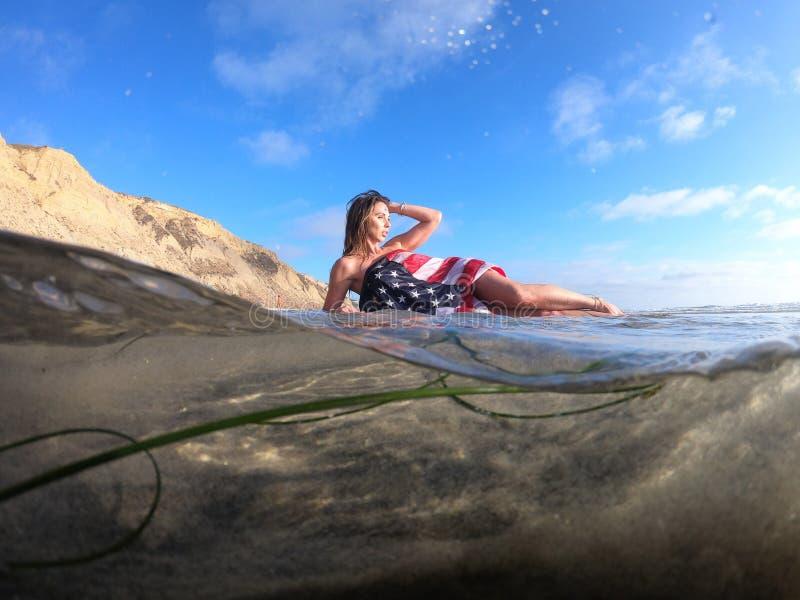 Un modelo moreno precioso Poses Nude At la costa con una bandera americana fotos de archivo