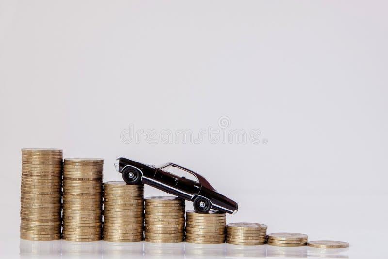 Un modelo negro de un coche con las monedas bajo la forma de histograma en un fondo blanco Concepto de pr?stamos, ahorros, seguro foto de archivo libre de regalías