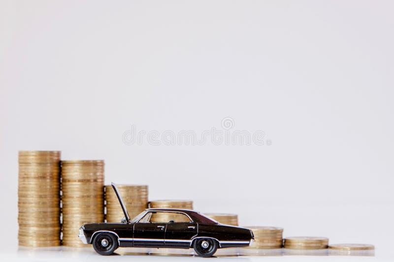 Un modelo negro de un coche con las monedas bajo la forma de histograma en un fondo blanco Concepto de pr?stamos, ahorros, seguro imagen de archivo libre de regalías