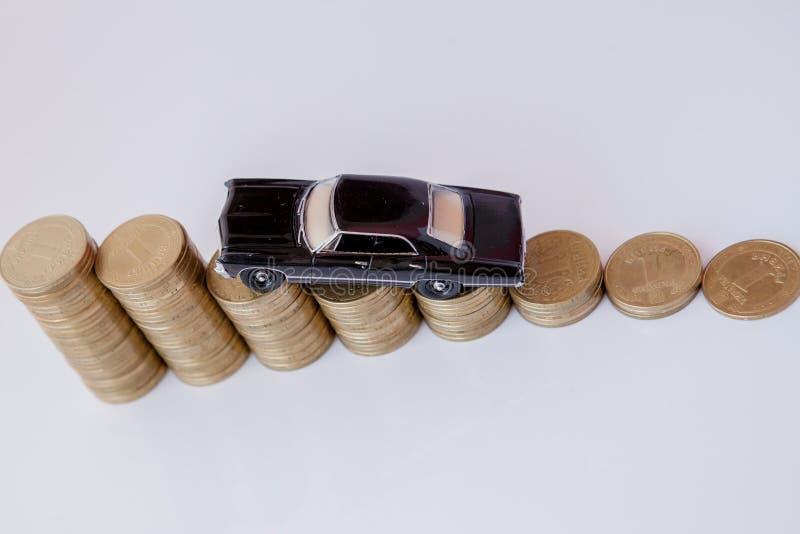 Un modelo negro de un coche con las monedas bajo la forma de histograma en un fondo blanco Concepto de pr?stamos, ahorros, seguro fotos de archivo libres de regalías