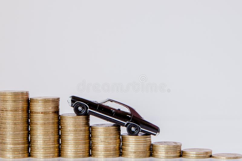 Un modelo negro de un coche con las monedas bajo la forma de histograma en un fondo blanco Concepto de pr?stamos, ahorros, seguro fotografía de archivo libre de regalías