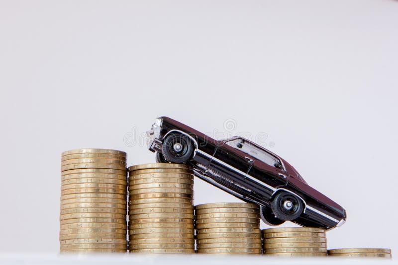 Un modelo negro de un coche con las monedas bajo la forma de histograma en un fondo blanco Concepto de pr?stamos, ahorros, seguro imagenes de archivo