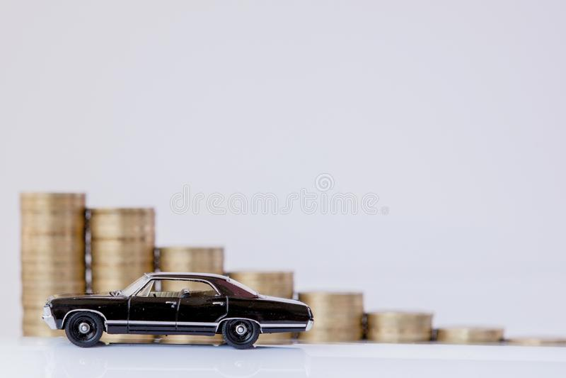 Un modelo negro de un coche con las monedas bajo la forma de histograma en un fondo blanco Concepto de pr?stamos, ahorros, seguro fotografía de archivo