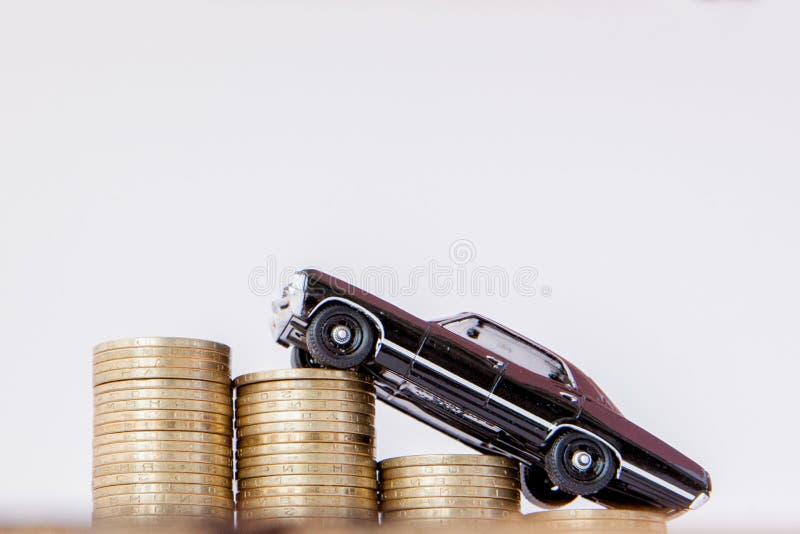 Un modelo negro de un coche con las monedas bajo la forma de histograma en un fondo blanco Concepto de pr?stamos, ahorros, seguro fotos de archivo