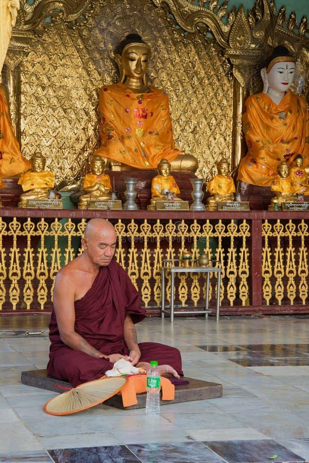 Un moine bouddhiste médite dans un des temples de la pagoda de Shwedagon Yangon, Myanmar photographie stock libre de droits