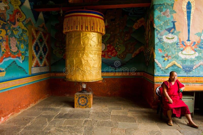 Un moine bouddhiste s'assied avec une grande prière roulent dedans le monastère de forteresse de Punakha, Paro, Bhutan image libre de droits
