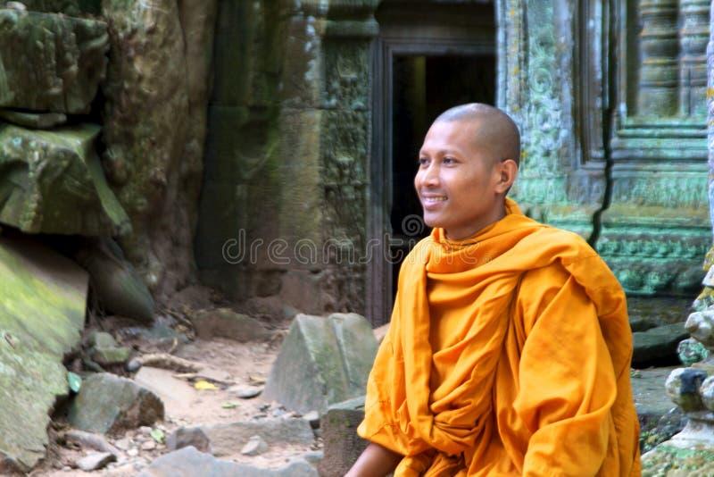 Un moine s'assied sur des ruines du temple de Ta Phrom photo libre de droits