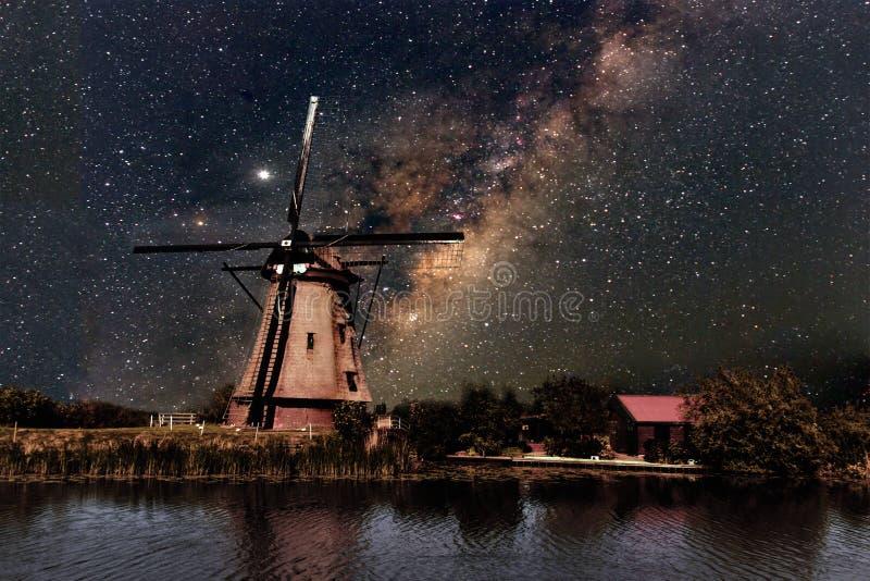 Un molino de viento y la vía láctea foto de archivo