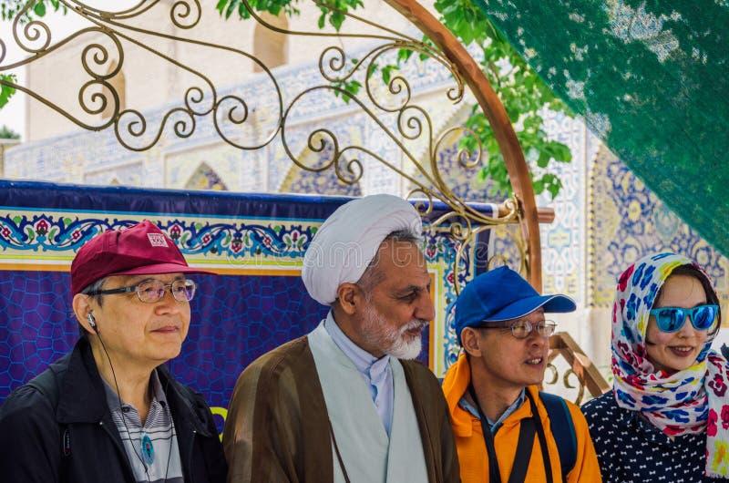 Un mollah iranien plus âgé portant un keffiyeh pose avec des touristes dans la cour de Jame Mosque image libre de droits