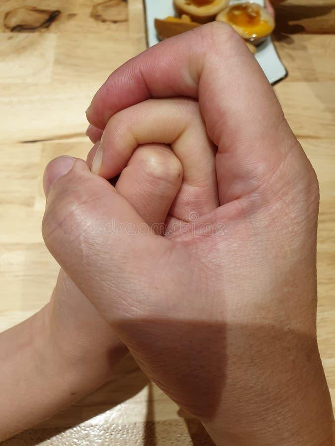 Un moment émouvant qui tenant la main d'un père sur sa fille images stock