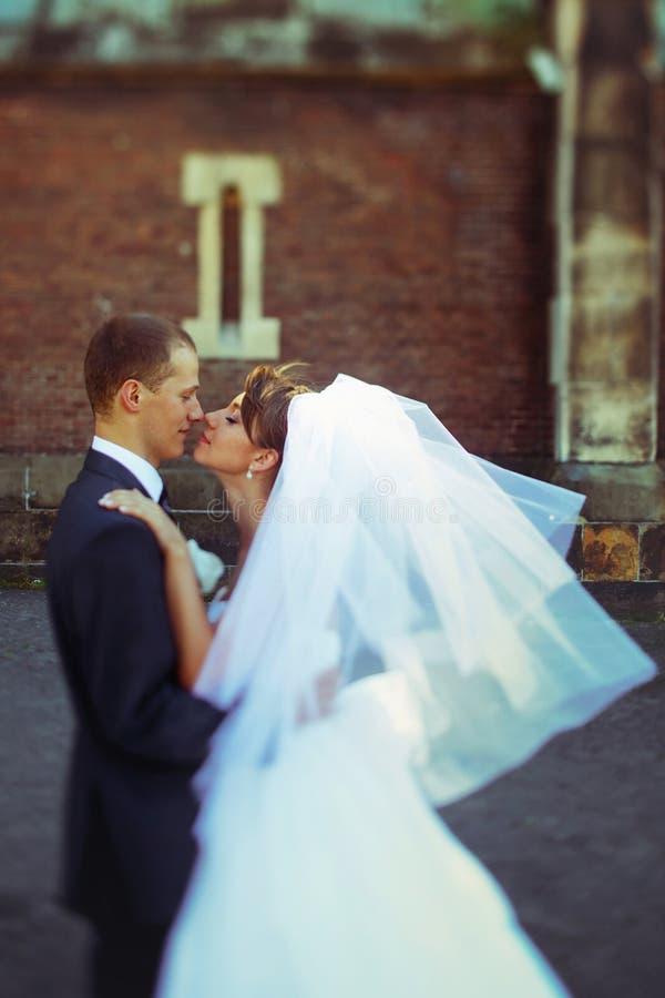 Un momento antes de un beso de los recienes casados que presentan en la calle foto de archivo