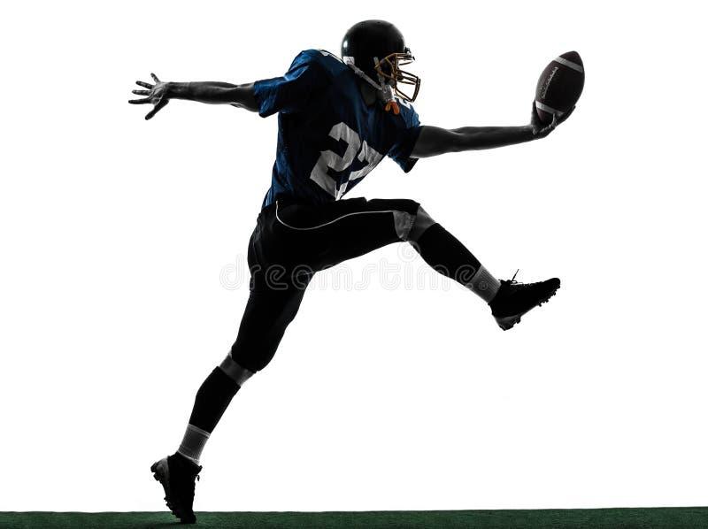 Silueta del momento del aterrizaje del hombre del jugador de fútbol americano que anota fotos de archivo