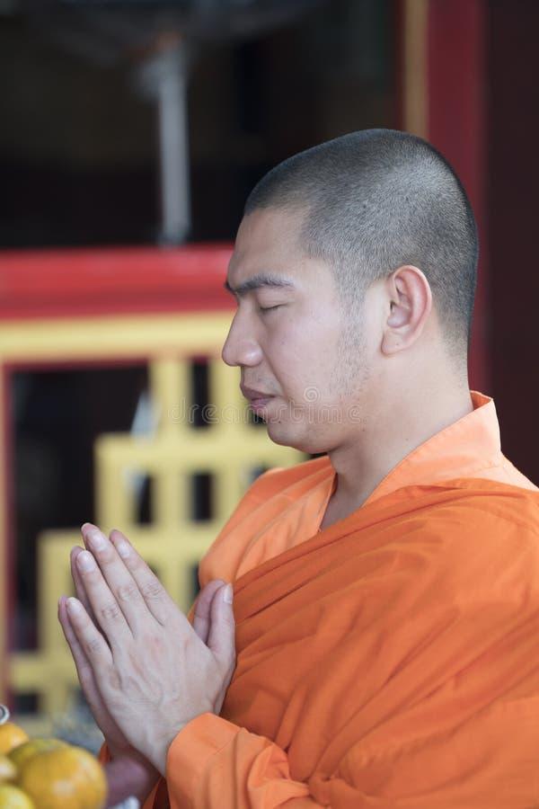 Un monaco buddista nella preghiera fotografia stock