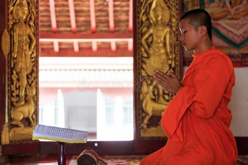 Un monaco che prega in tempio del Laos fotografie stock