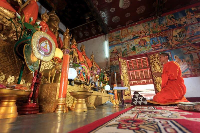 Un monaco che prega in tempio del Laos fotografie stock libere da diritti