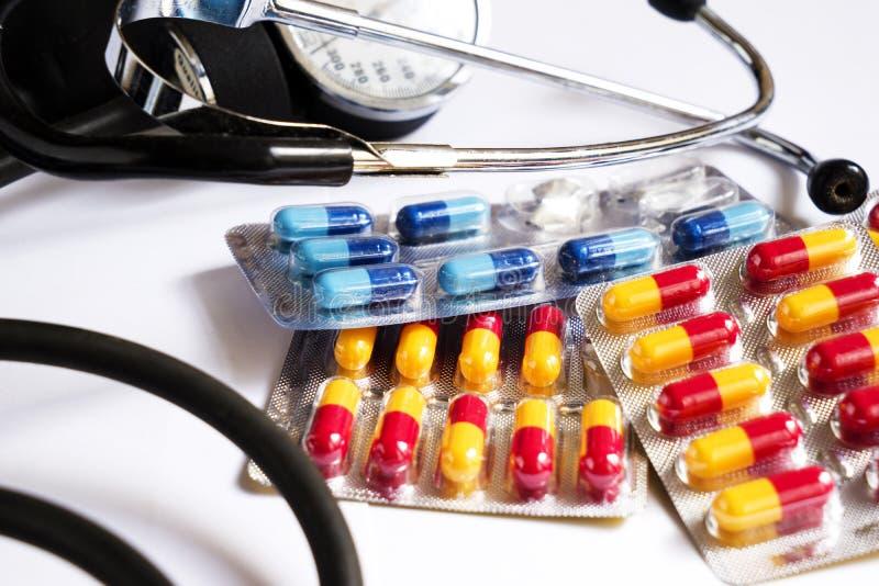 Un monitor e medicine di pressione sanguigna in capsule colorate differenti fotografia stock libera da diritti