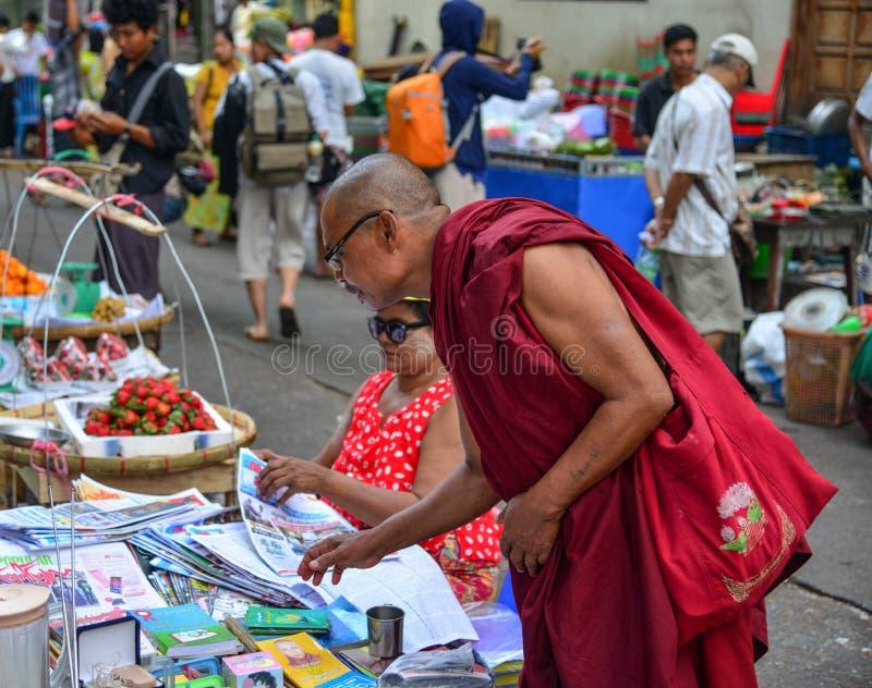 Un monje en el mercado en Rang?n, Myanmar foto de archivo