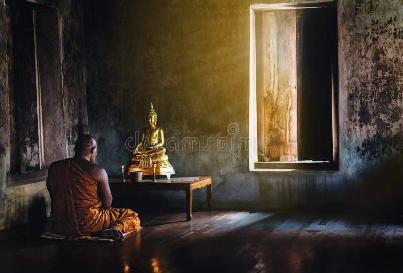 Un monje es que adora y que medita delante del Buddh de oro imagen de archivo libre de regalías