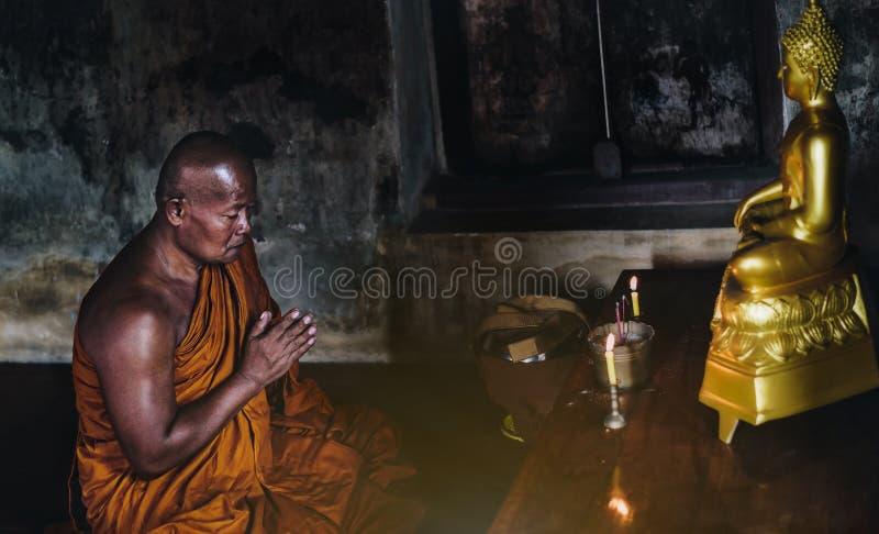 Un monje es que adora y que medita delante del Buddh de oro fotos de archivo libres de regalías
