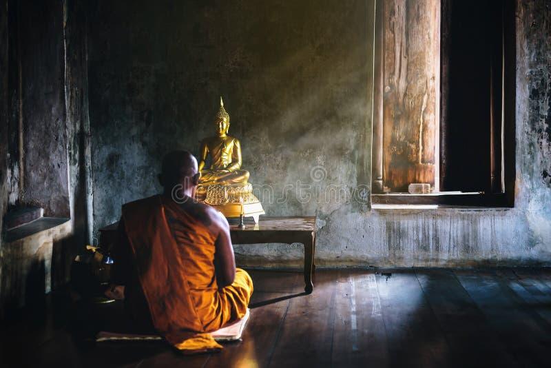 Un monje es que adora y que medita delante del Buddh de oro imágenes de archivo libres de regalías