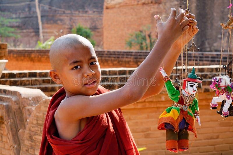 Un monje joven que juega las marionetas en Bagan, Myanmar foto de archivo