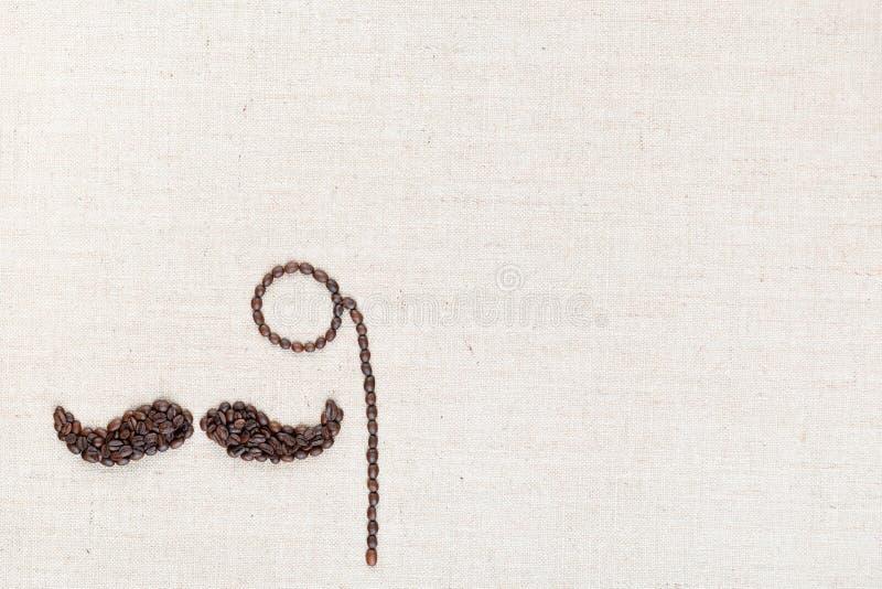 Un monocle et une moustache faits avec des grains de café tirés à partir d'en haut, aligné au en bas à gauche W photo stock