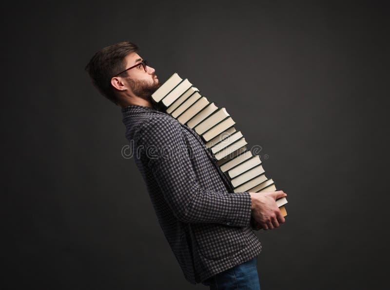 Un montón que lleva del hombre de libros foto de archivo libre de regalías