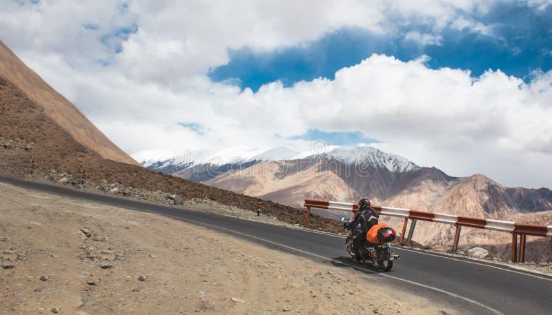 Un montar a caballo del jinete de la bici en los caminos con curvas de Himalaya a Leh, Ladakh fotografía de archivo libre de regalías