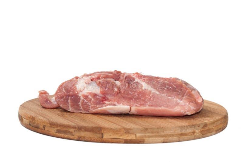 Un morceau d'épaule de porc sur le panneau en bois de cuisine images libres de droits