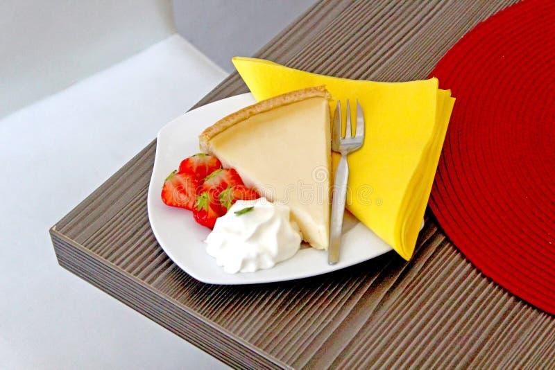 Un morceau de cheescake avec des fraises d'un plat blanc sur une table en bois image libre de droits