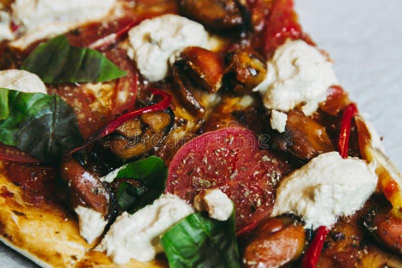 Un morceau de coupes végétariennes faites maison fraîchement cuites au four de pizza avec la fin de tofu de tomates de moules  photos stock