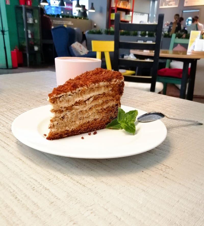 Un morceau de gâteau brun d'un plat blanc sur une table dans une feuille en bon état de café photographie stock libre de droits