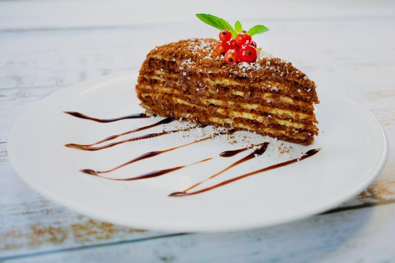 Un morceau de gâteau de chocolat avec des baies et des feuilles en bon état d'un plat, sur une table en bois légère images libres de droits