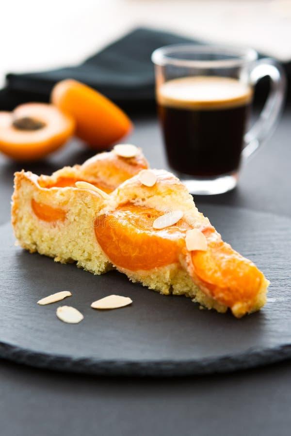 Un morceau de gâteau d'abricot avec des rubans d'amande sur une ardoise ronde noire photo stock