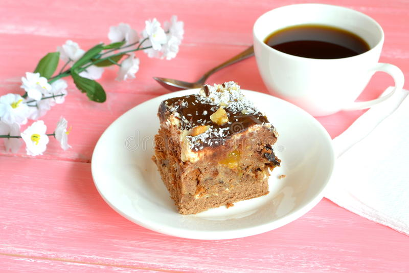Un morceau de gâteau d'un plat, cuillère, serviette blanche, tasse de café sur la table en bois blanche photos stock