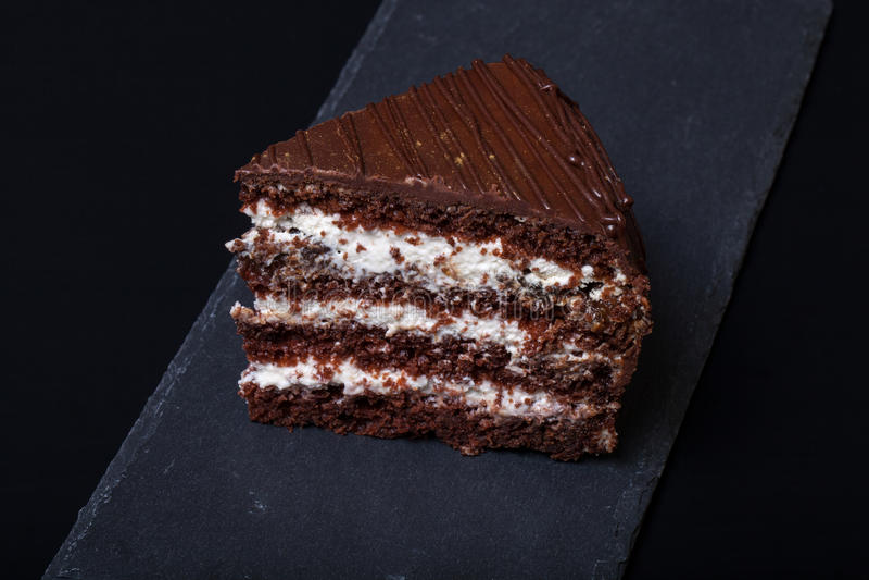 Un morceau de gâteau de chocolat de plat d'ardoise sur le fond noir photographie stock