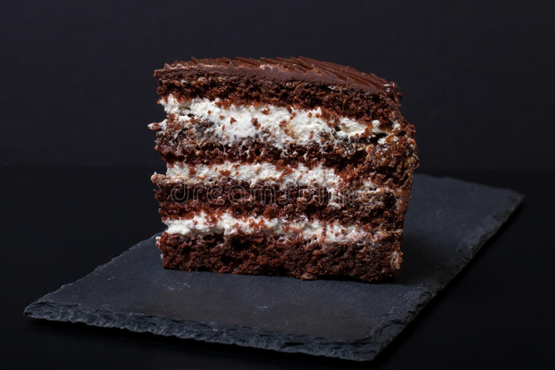 Un morceau de gâteau de chocolat de plat d'ardoise sur le fond noir Se image stock