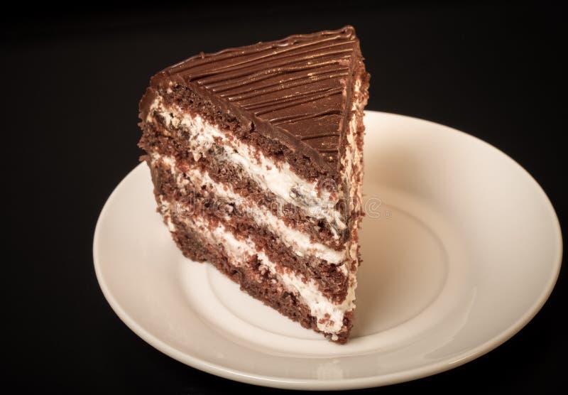 Un morceau de gâteau de chocolat du plat blanc sur le fond noir À photos stock